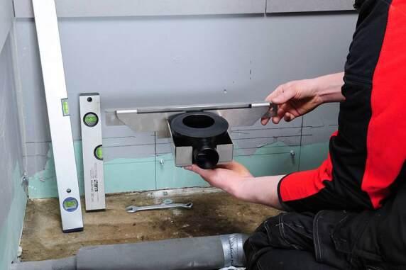 Die zwei Komponenten des Abflusssystems des Duschboards: Wandhalterung und Siphon.
