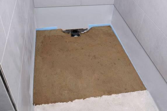 Der Duschbereich wird mit Estrich oder alternativ mit Mörtelsäcken aufgefüllt. Dabei ist das Gefälle des Duschboards beizubehalten.