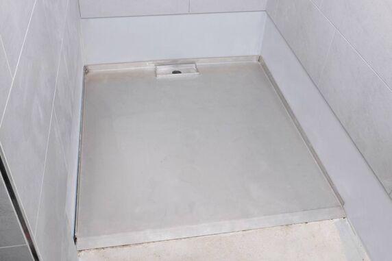 Fliesenkleber stellt erste die Verbindung des Edelstahl-Duschboards zur Wand her.
